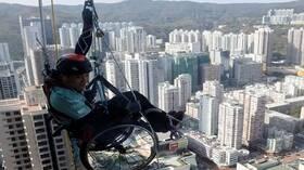 صيني على كرسي المعاقين  يتسلق أعلى  ناطحة سحاب في هونغ كونغ