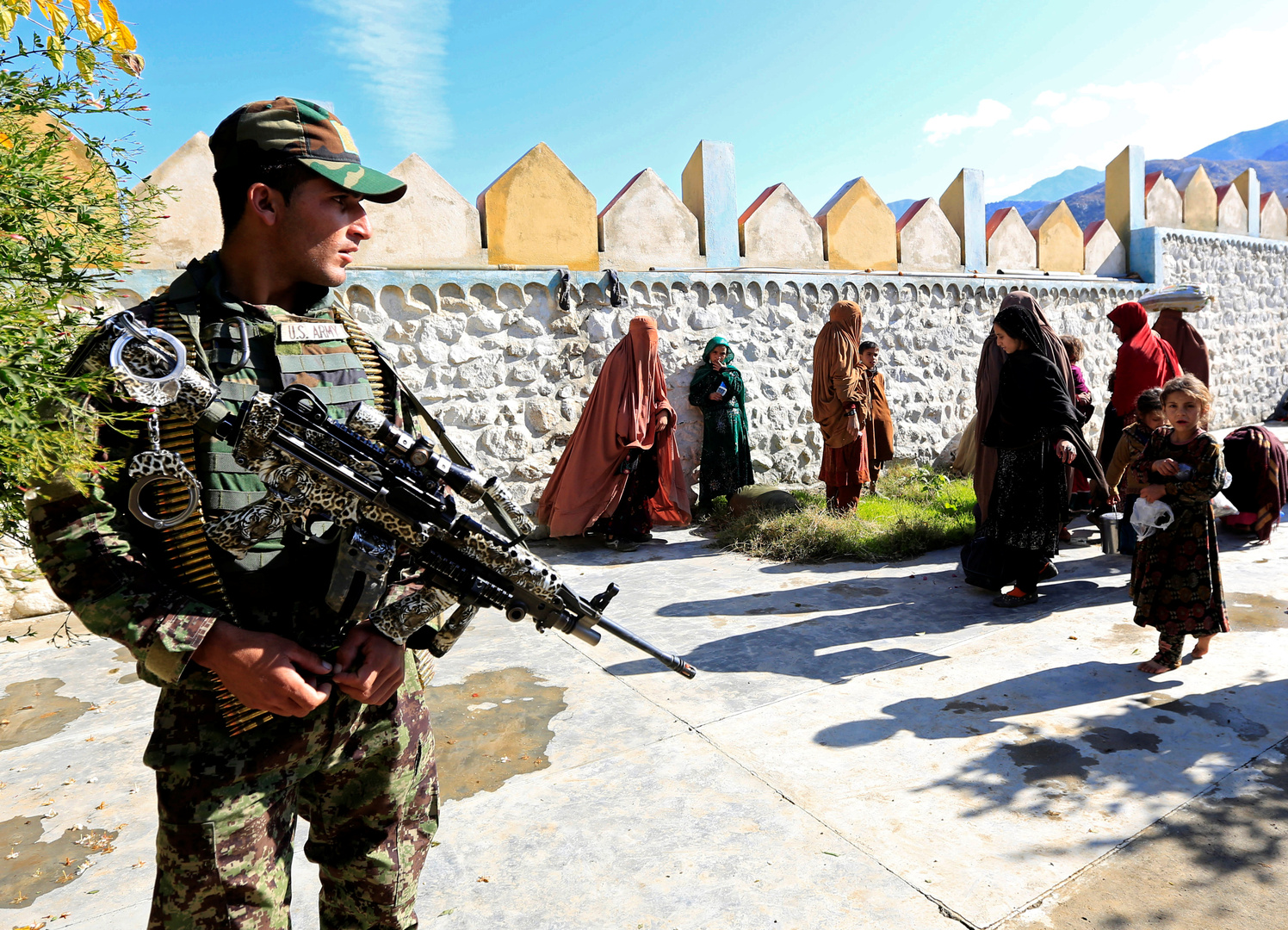 عنصر من قوات الأمن الأفغانية يراقب بجانب أفراد عائلات مسلحي