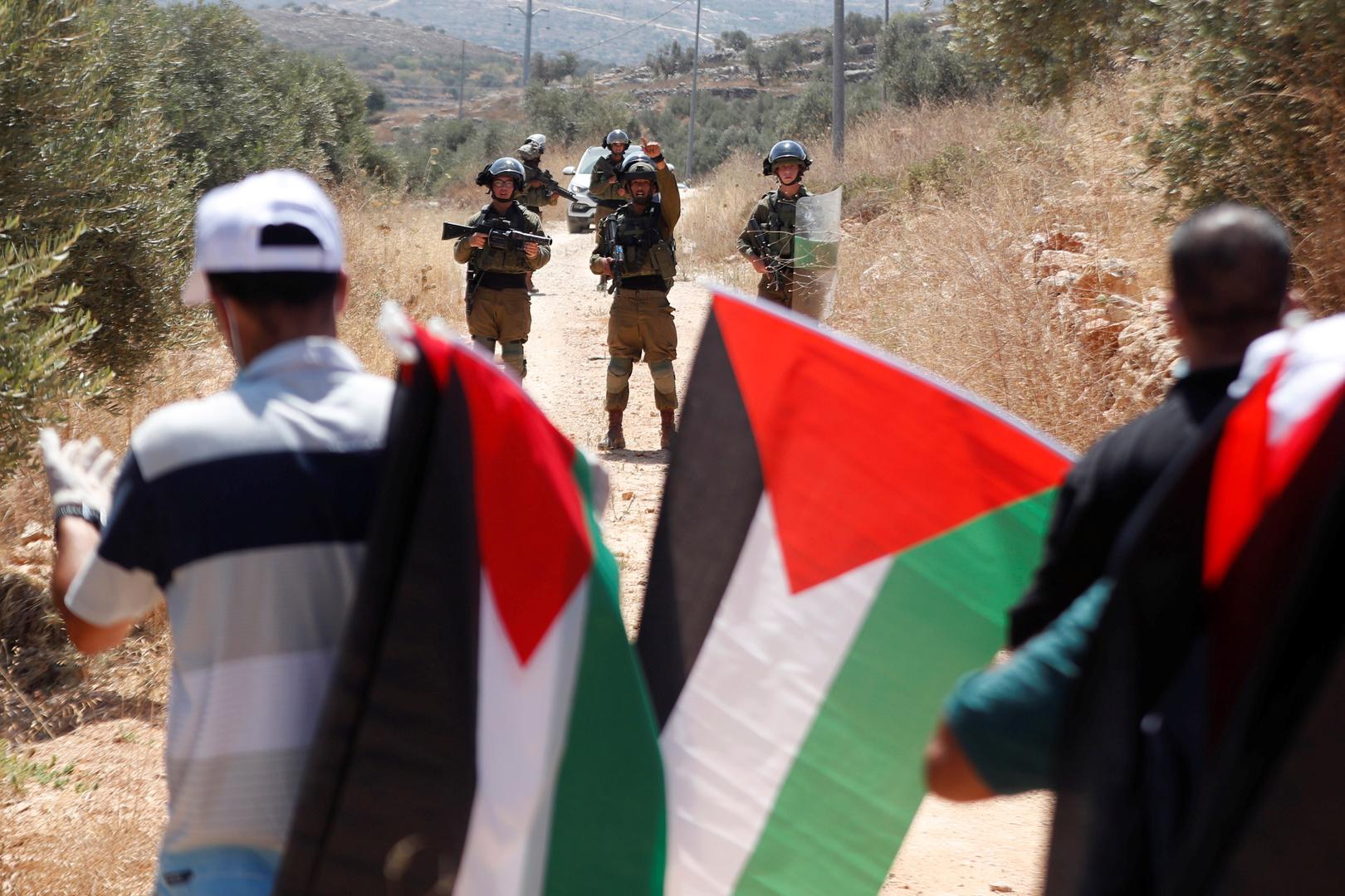 مواطنون يحملون الأعلام الفلسطينية وبوجههم جنود من الجيش الإسرائيلي