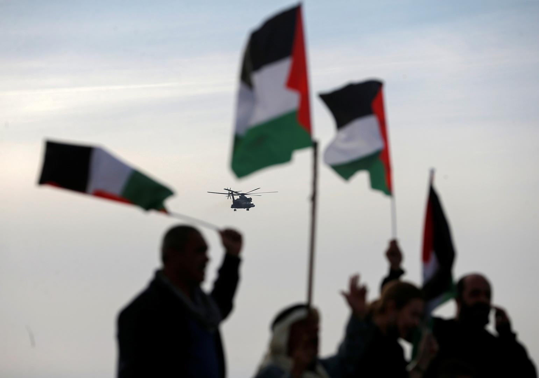 مواطنون يحملون الأعلام الفلسطينية ومروحية تحلق في السماء