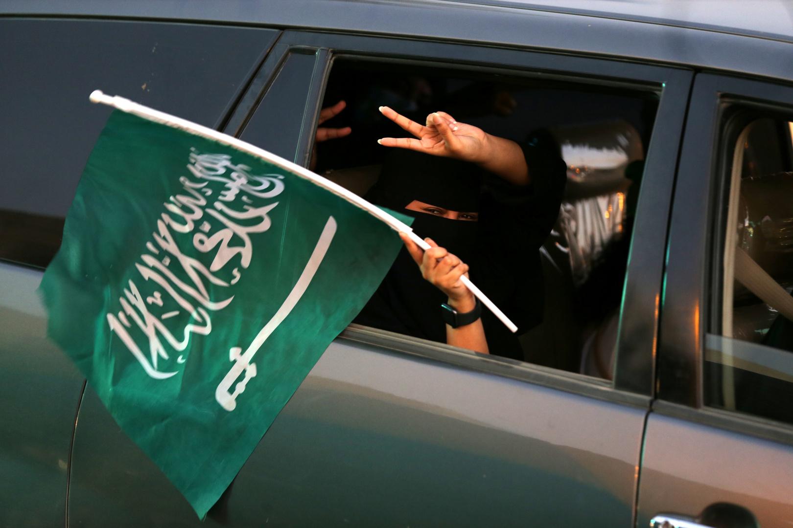 مواطنة تجلس في سيارة وتحمل العلم السعودي
