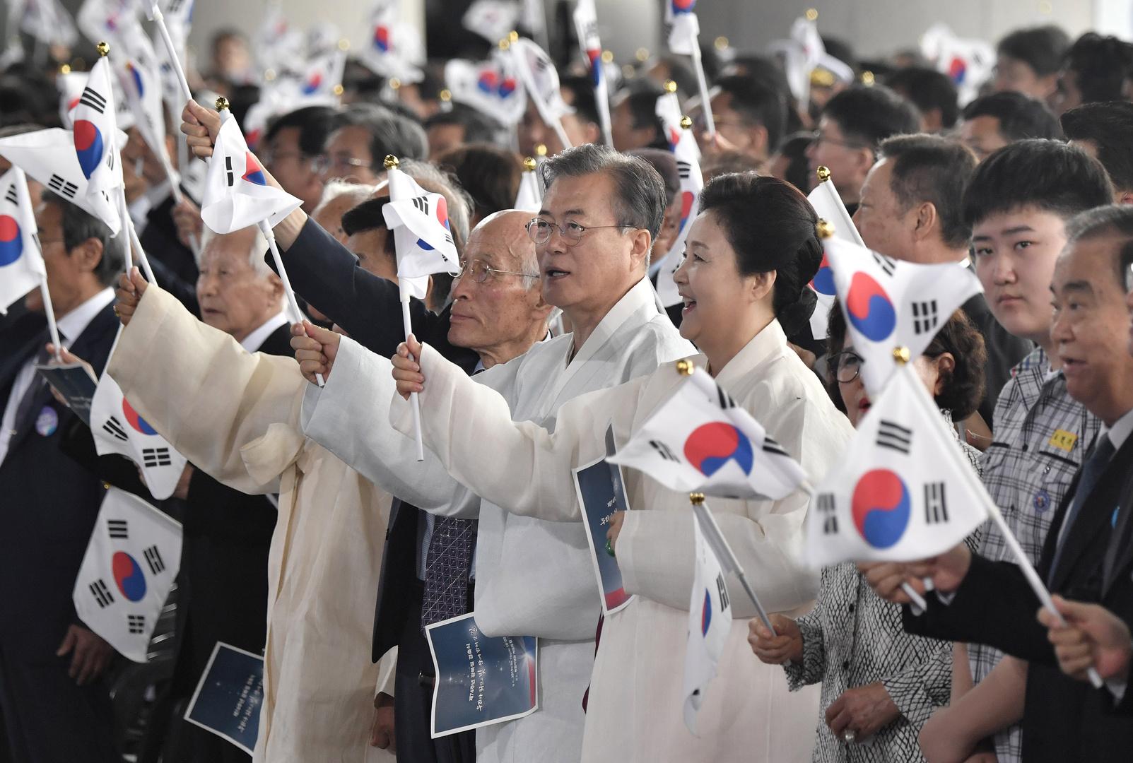 الرئيس الكوري الجنوبي مون جيه إن وزوجته كيم جونغ سوك وجمع من الناس يلوحون بالأعلام الكورية الجنوبية