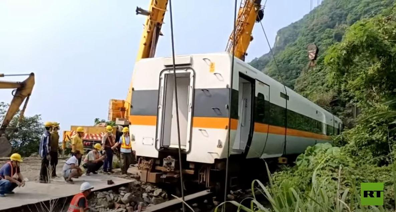 عمال يعيدون القطار المنكوب إلى السكّة