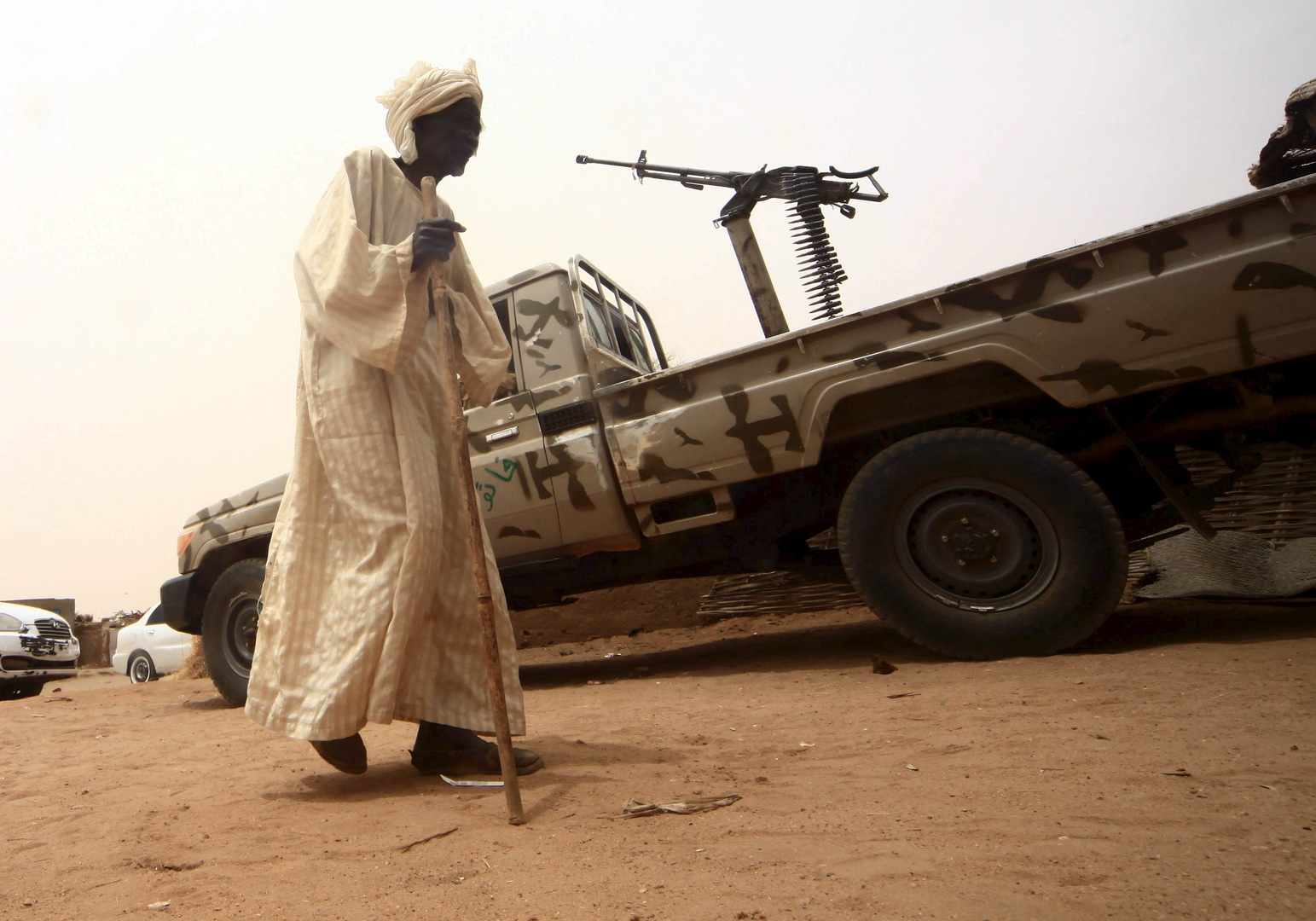 رجل يمشي بجانب آلية عليها رشاش في دارفور بالسودان