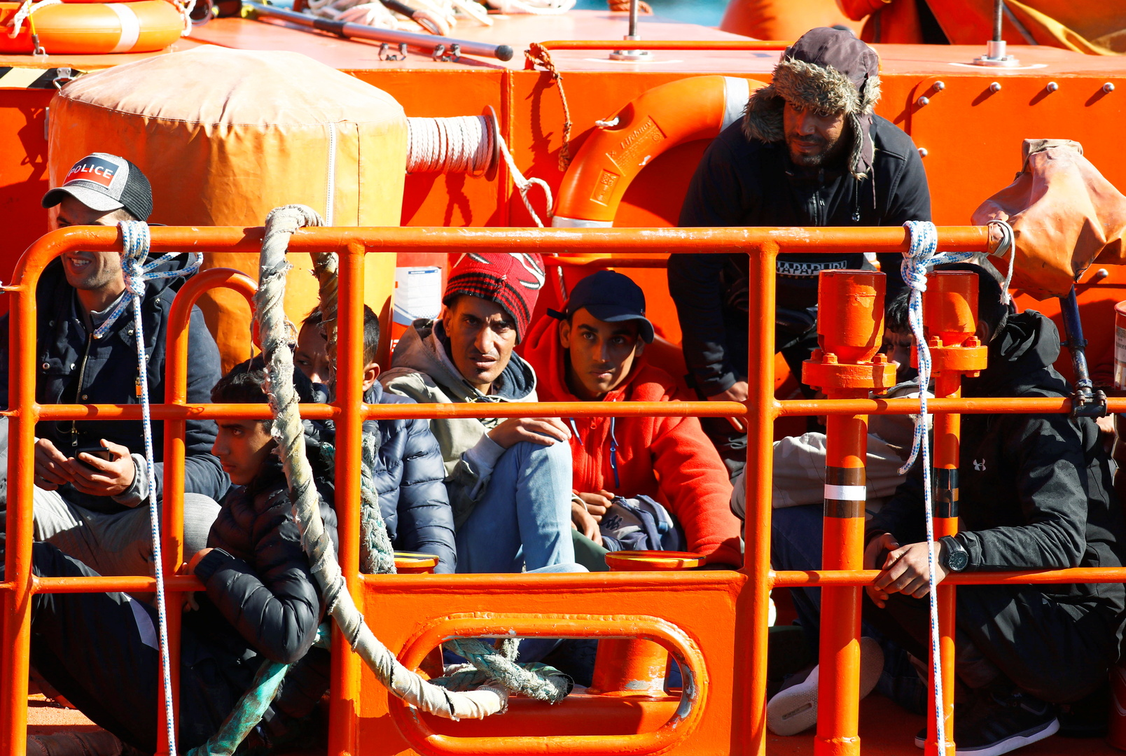 مهاجرون ينتظرون النزول من سفينة تابعة لخفر السواحل الإسبانية في ميناء أرغوينيجين