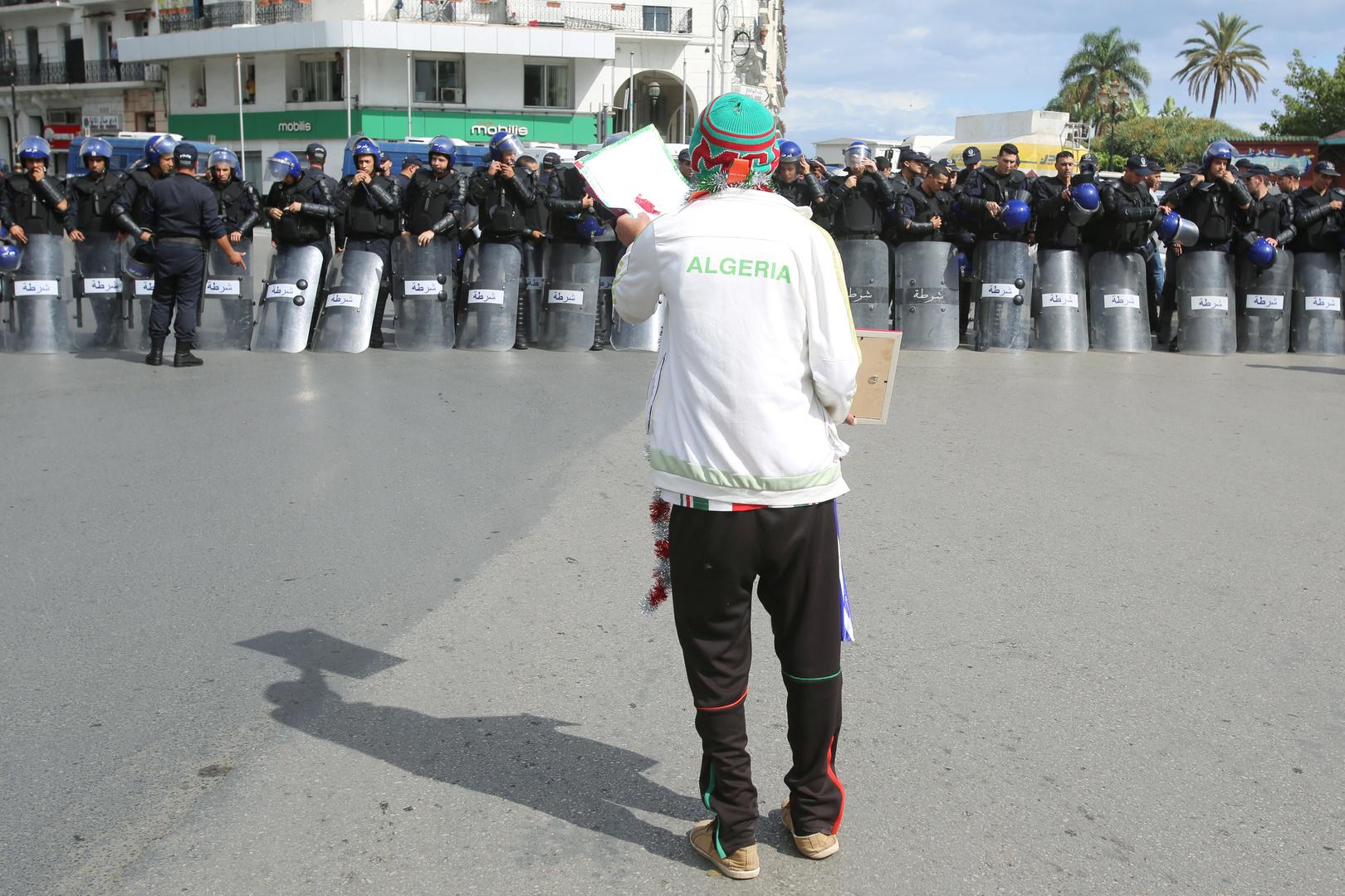 مواطن جزائري يقف أمام عناصر من الشرطة الجزائرية