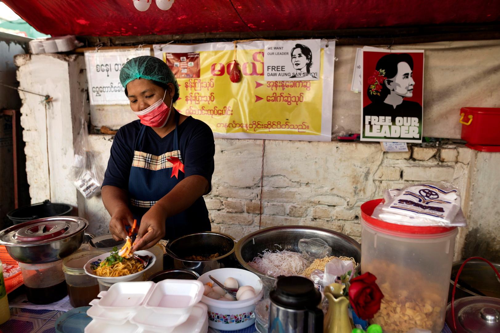 امرأة تطبخ في كشك للطعام عليه ملصقات ضد الانقلاب العسكري في يانغون، ميانمار، 16 فبراير 2021