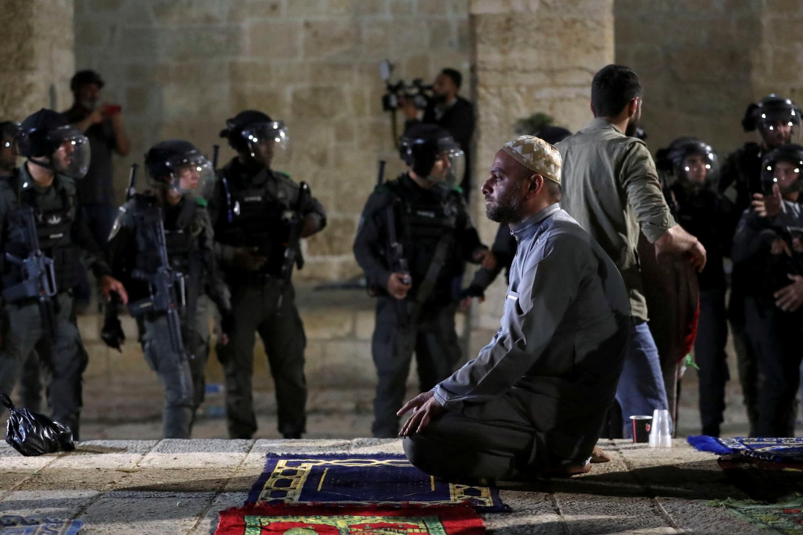فلسطيني يصلي بينما تتجمع الشرطة الإسرائيلية خلال مواجهات المسجد الأقصى