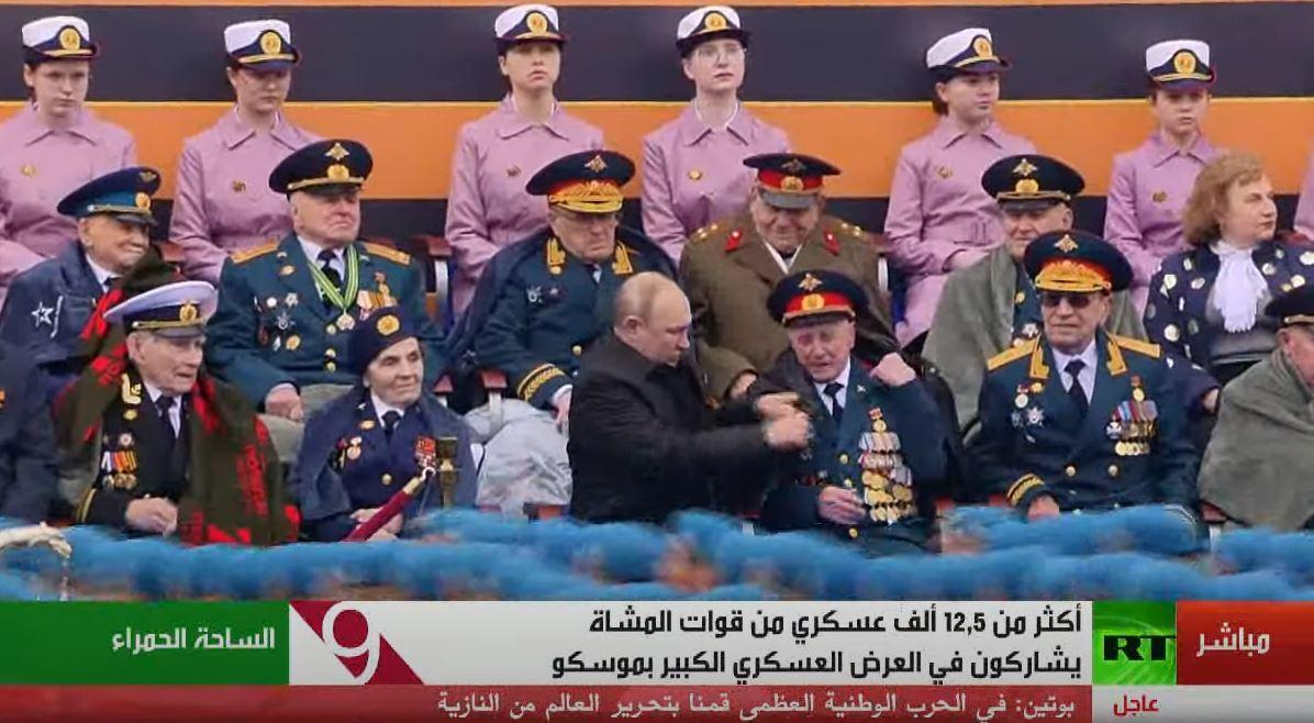 بوتين يساعد أحد المحاربين في ارتداء المعطف أثناء العرض العسكري في الساحة الحمراء