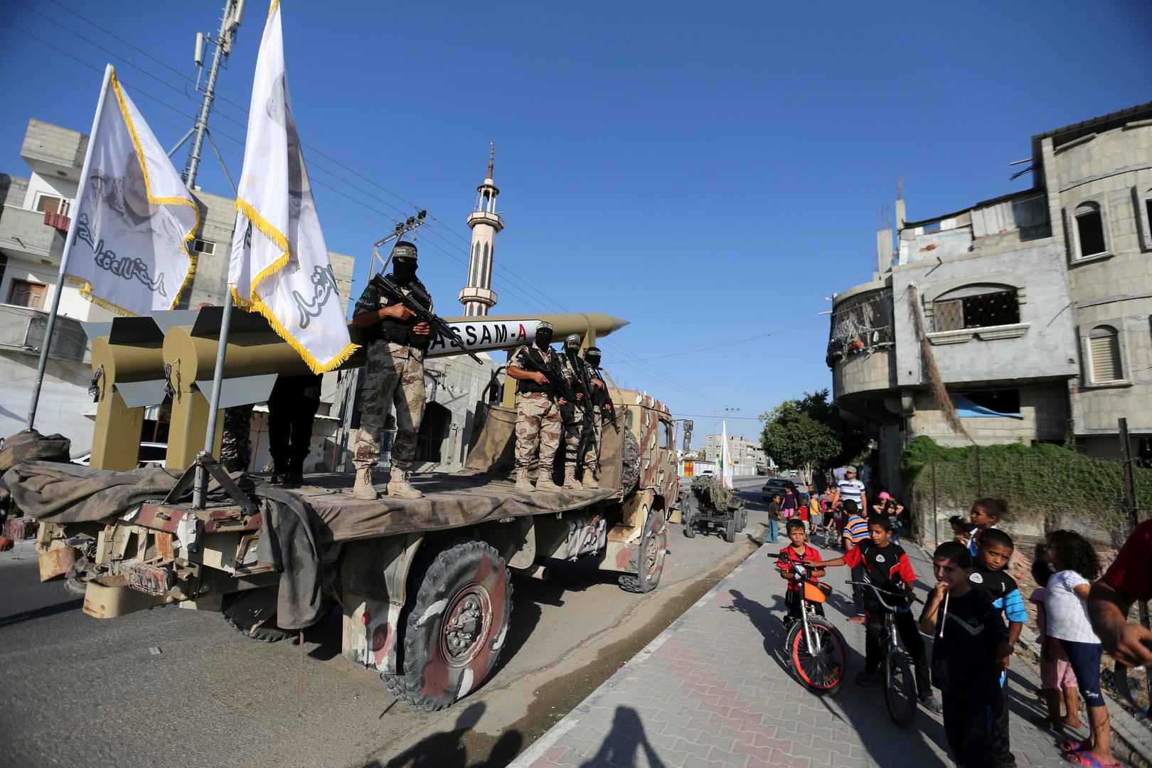 """عناصر من كتائب القسام، الجناح العسكري لحركة """"حماس""""، يعرضون صواريخ محلية الصنع خلال عرض عسكري."""