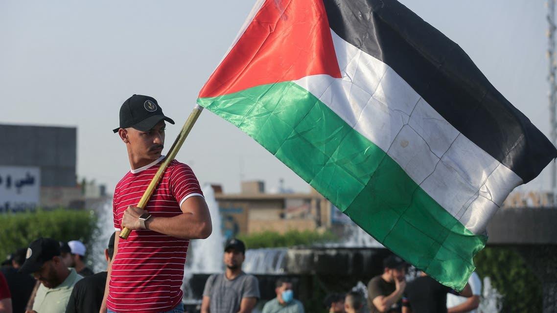 شاب عراقي يحمل العلم الفلسطيني