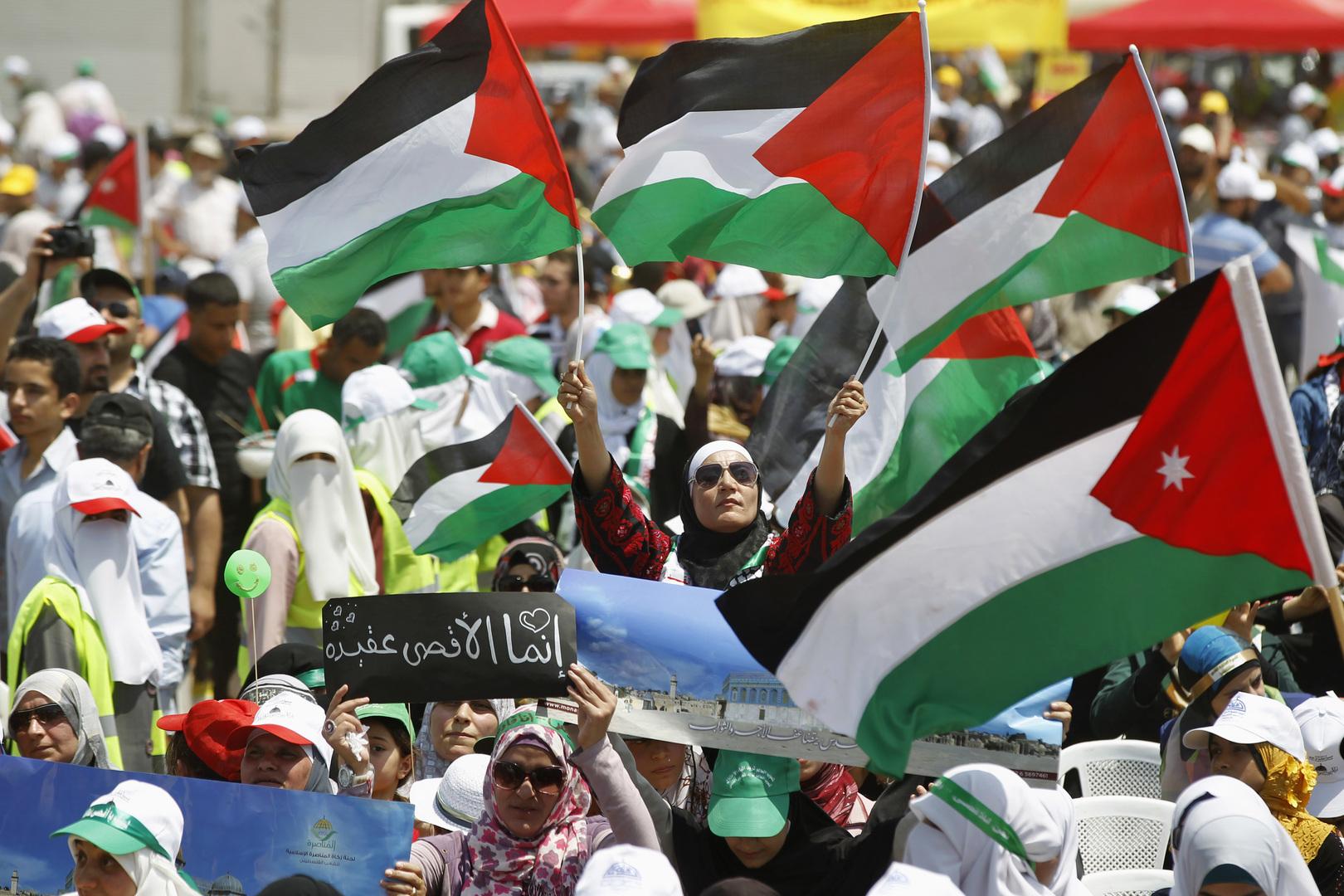 مواطنون يحملون العلم الفلسطيني والعلم الأردني