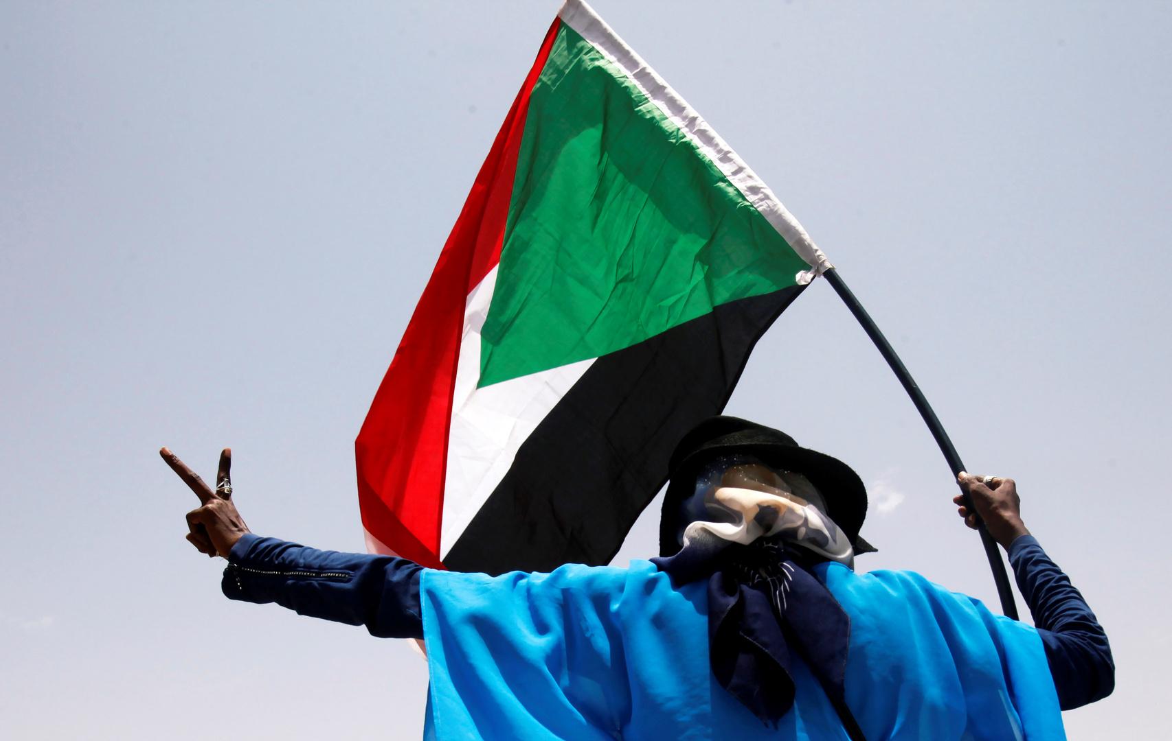 مواطن سوداني يرفع علم السودان