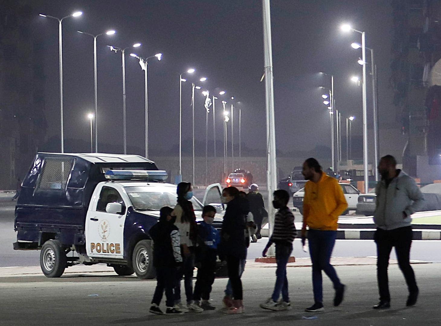 مواطنون يمشون أمام آلية تابعة للشرطة المصرية