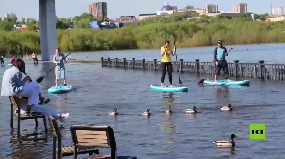 شاهد.. أهالي مدينة روسية يستقبلون الفيضانات بفرح!