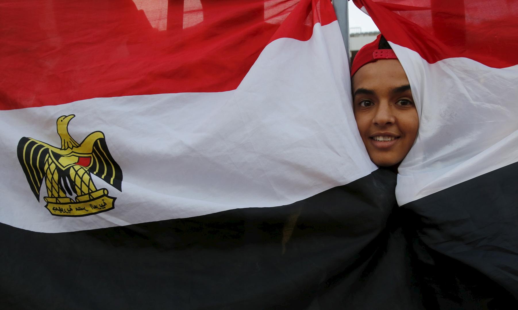 طفل يبرز وجهه من بين علمين لمصر