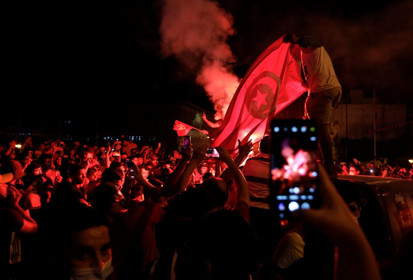 تونسيون يحتفلون بقرارات رئيس البلاد، قيس سعيد، لإقالة الحكومة وتجميد عمل البرلمان.