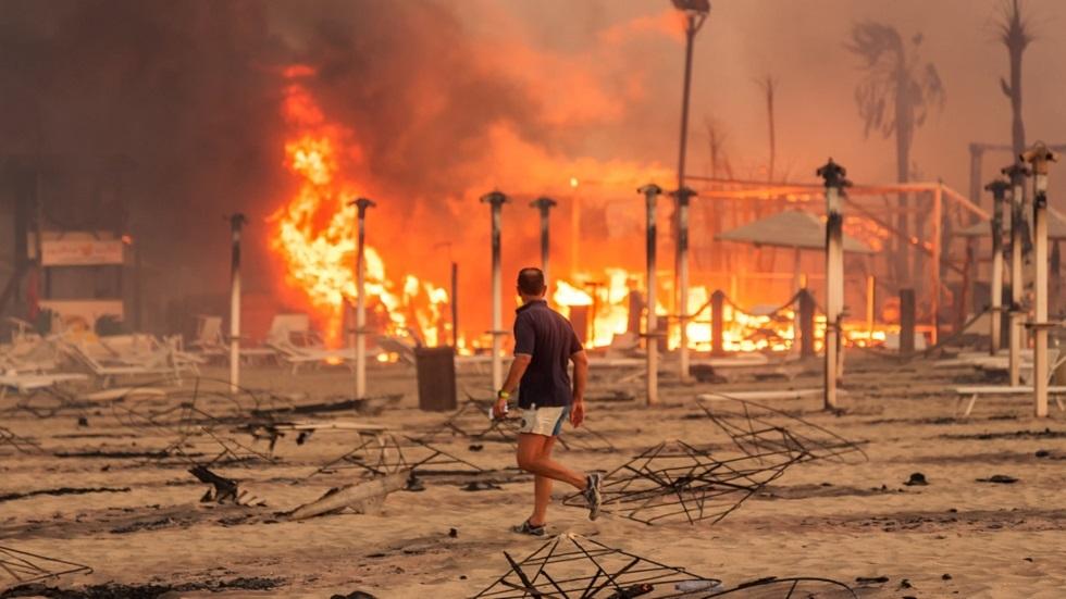 رجل يمشي أمام حريق في شاطئ  في كاتانيا، صقلية، إيطاليا