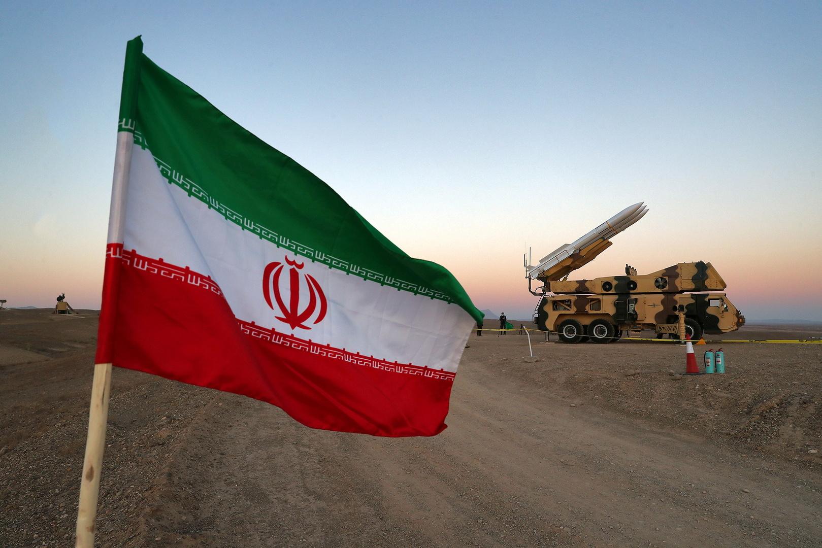 العلم الإيراني أمام راجمة صواريخ