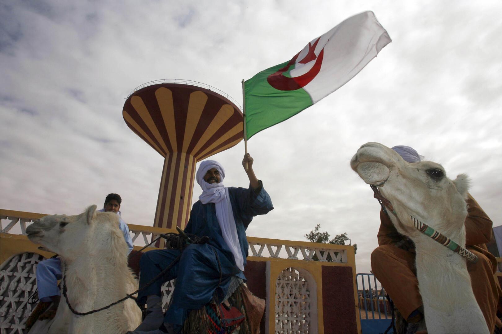 مواطن يمتطي جمل ويحمل العلم الجزائري