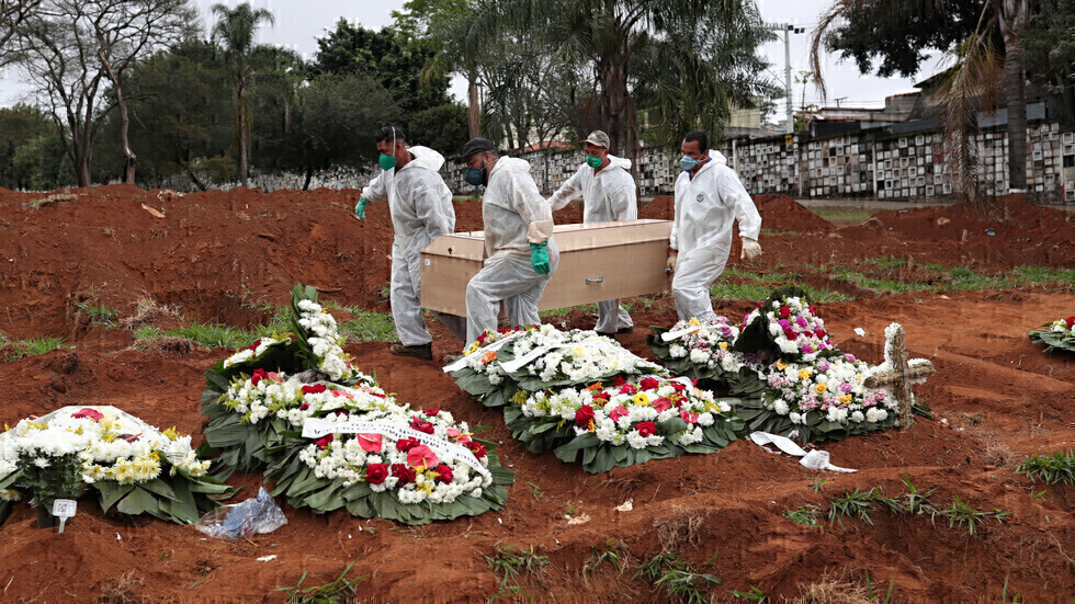 موظفو مكتب جنازة بنقلون تابوتا فيه جثمان شخص متوف بفيروس كورونا في مدينة ساو باولو البرازيلية.