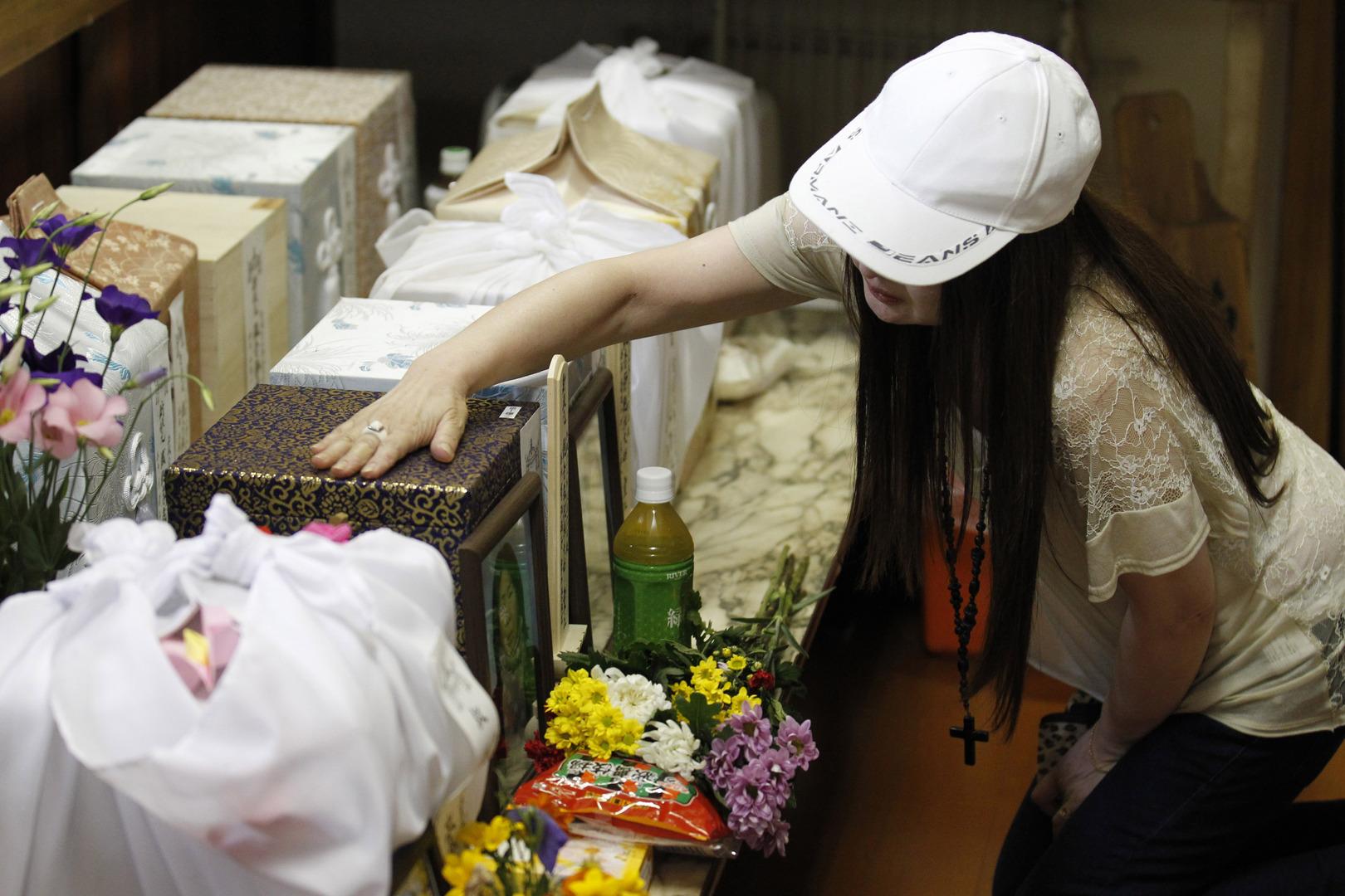 صورة تعبيرية لسيدة تلمس الصناديق التي تحتوي على رماد والدتها