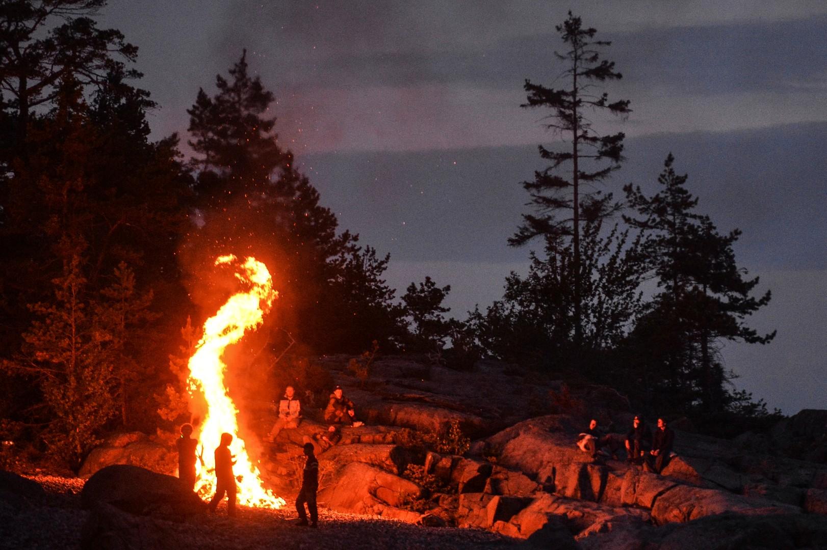 Участники экологической вахты сжигают собранный мусор на берегу Финского залива во время комплексной экспедиции Русского географического общества «Гогланд» на острове Гогланд.