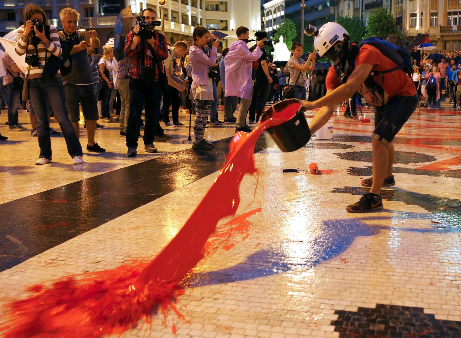 Протестующие заливают красной краской площадь в центре Скопье.