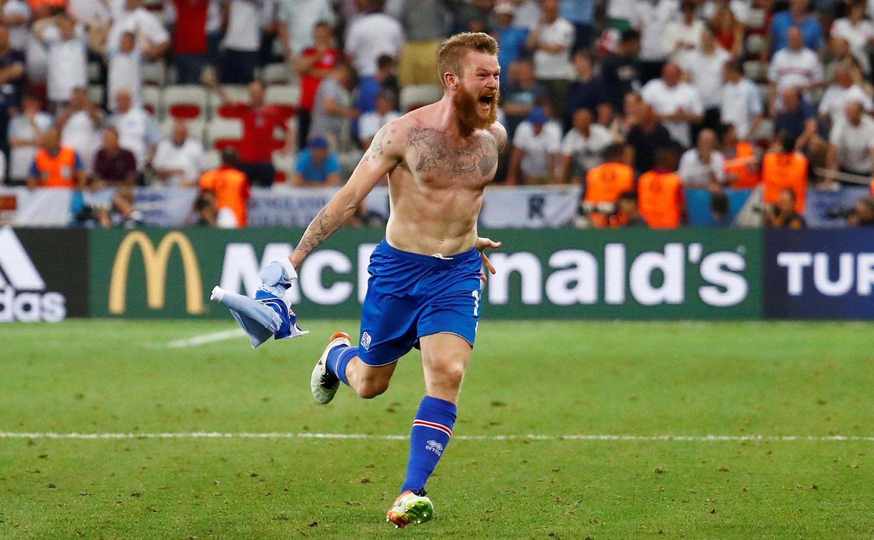 Полузащитник сборной Исландии Арон Гуннарссон празднует победу своей команды над Англией.