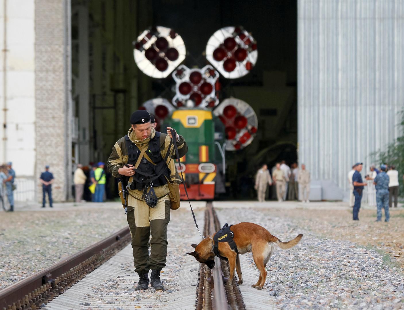 Сотрудник полиции со служебной собакой проверяет железную дорогу на космодроме Байконур в Казахстане