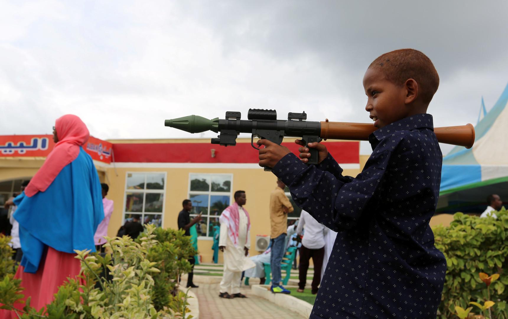 Сомалийский мальчик с игрушечным оружием в руках после молитвы в честь окончания священного месяца Рамадан.