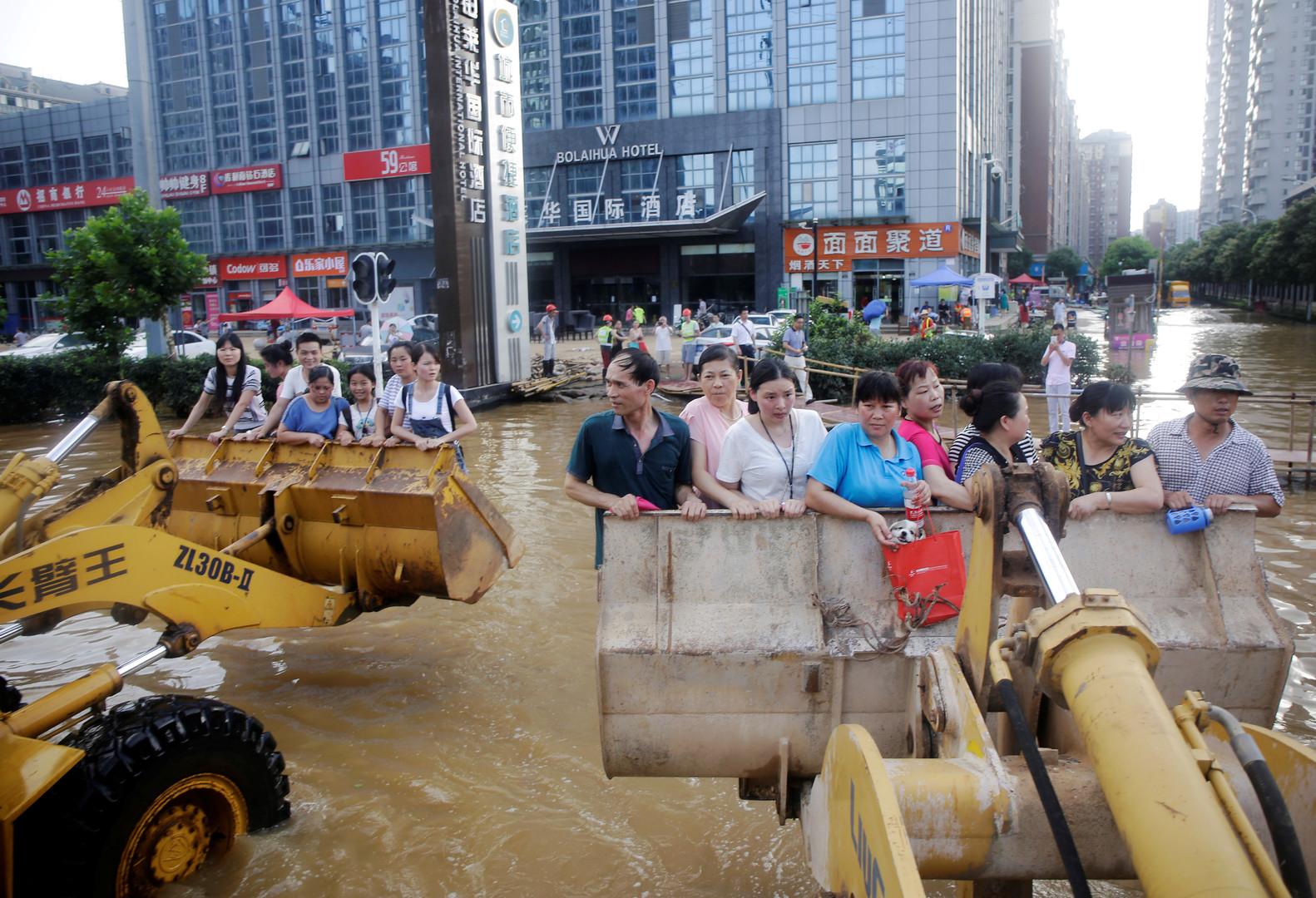 Тайфун в Китае. В затопленном китайском городе Ухань люди добираются до работы в ковшах экскаваторов.