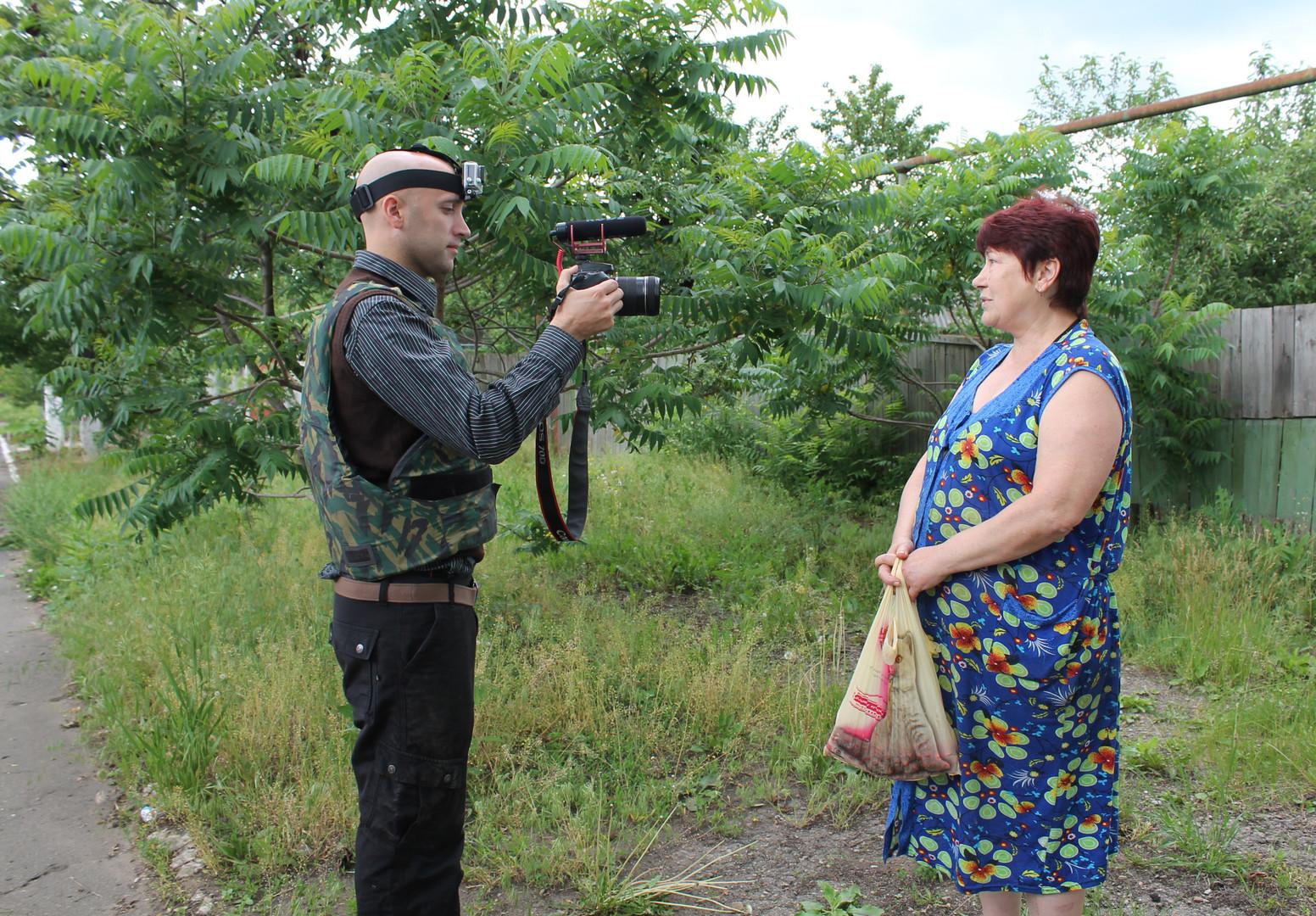 Британский журналист Грэм Филипс берет интервью у жительницы города Горловки Донецкой области.