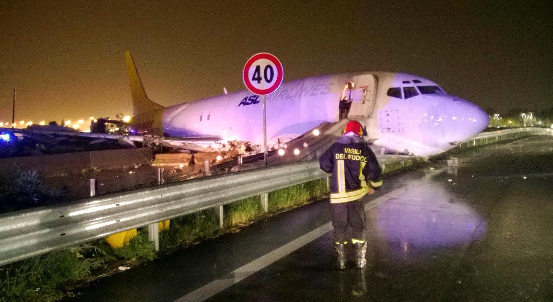 Пожарные возле потушенного грузового авиалайнера, выкатившегося за пределы взлетно-посадочной полосы в аэропорту Орио-аль-Серио в 3 км от итальянского Бергамо.