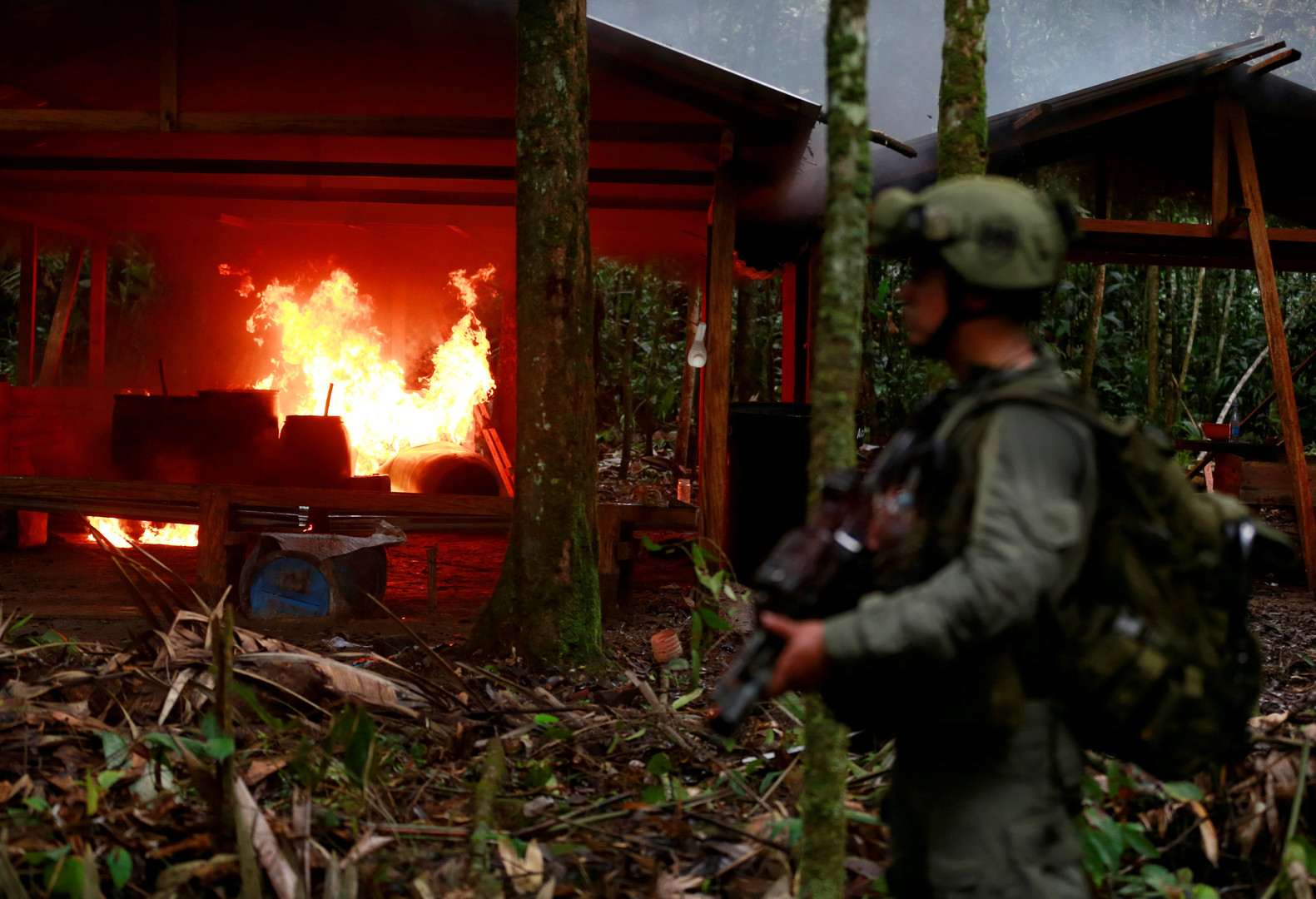 Сотрудник колумбийской полиции по борьбе с наркотиками охраняет территорию, пока его коллеги уничтожают лабораторию в деревне Каламар, где производился кокаин.