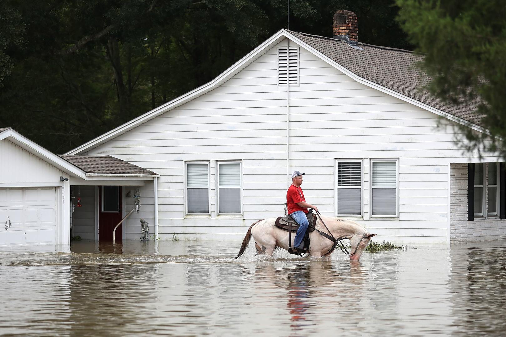 Ковбой передвигается по затопленной дороге в американском штате Луизиана, где несколько дней не прекращались проливные дожди.