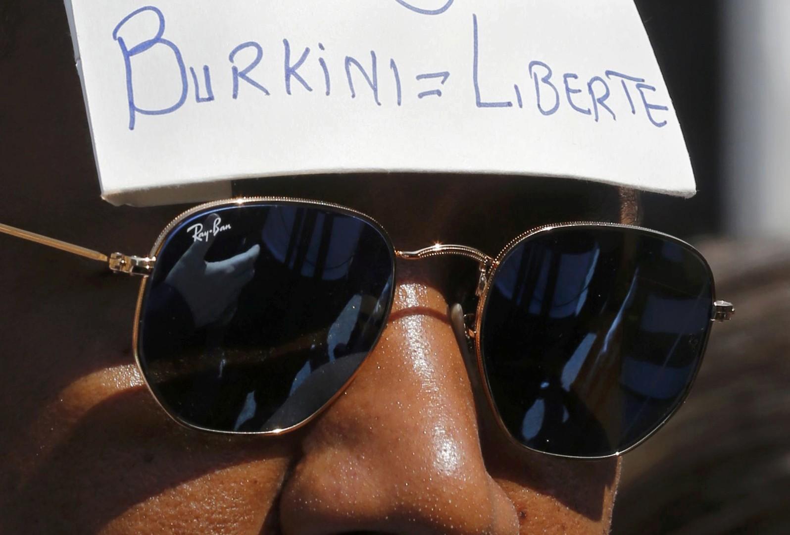 Госсовет Франции приостановил действие постановления мэрии города Вильнёв-Лубе, запрещающего ношение мусульманского купального костюма буркини. Надпись у мужчины «буркини = свобода»