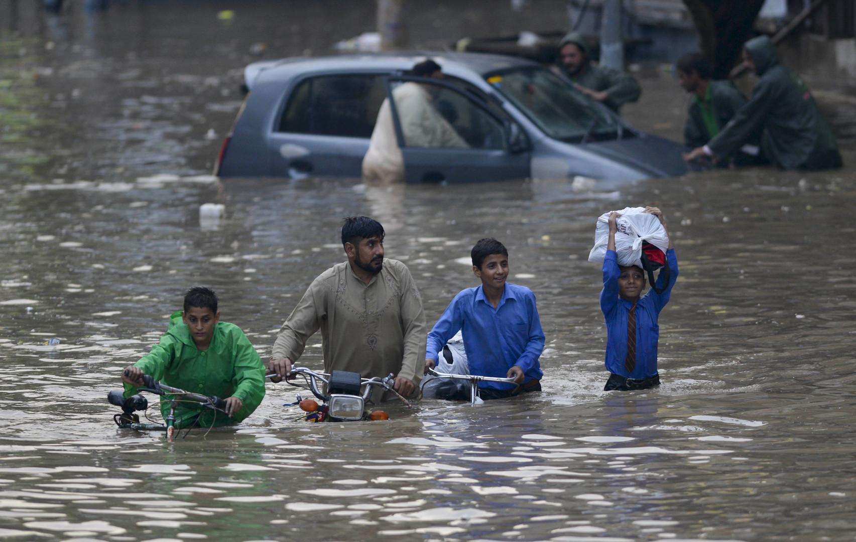 Пакистанцы с велосипедами и мотоциклом пересекают улицу в Лахоре, затопленную в результате сильных ливней.