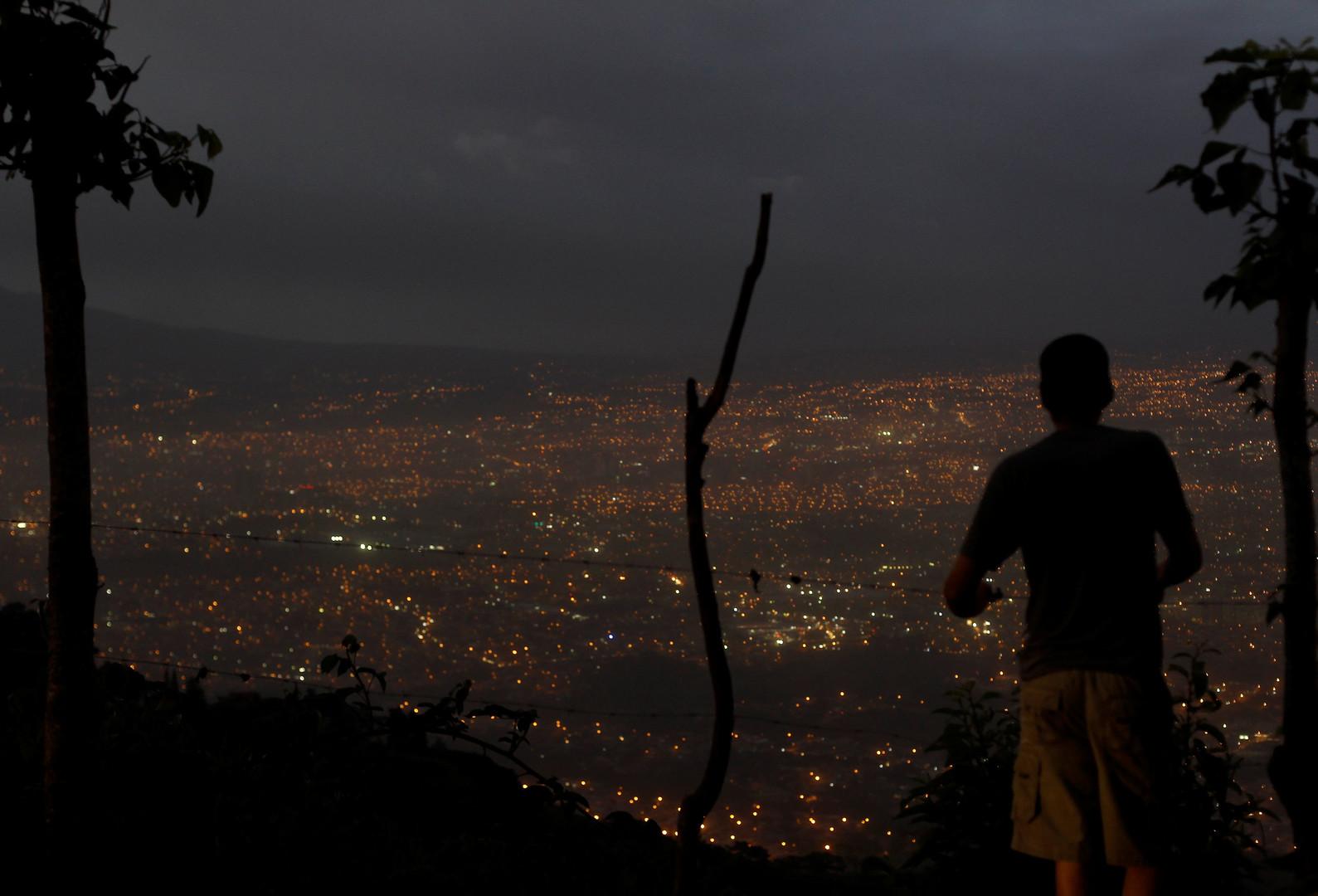 Житель Сан-Хосе наблюдает за тем, как на город опускается пепел от извержения  Турриальбы.