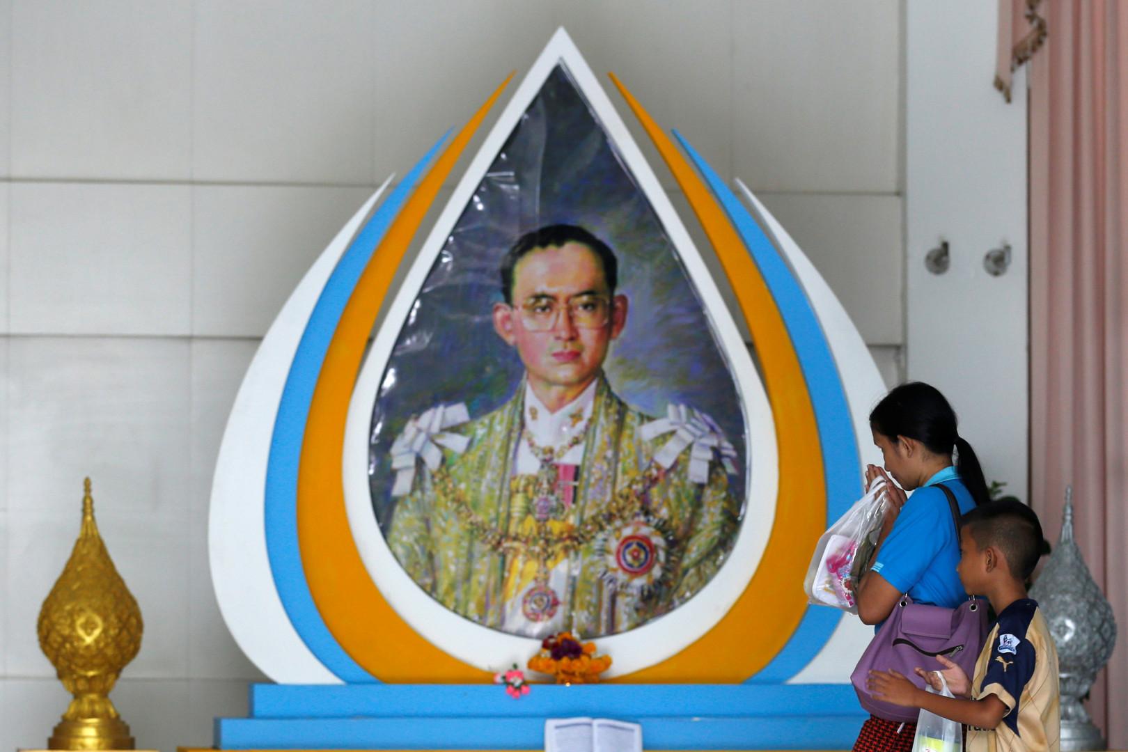 Доброжелательница молится перед изображением короля Пхумипона Адульядета в больнице Сирират в Бангкоке.