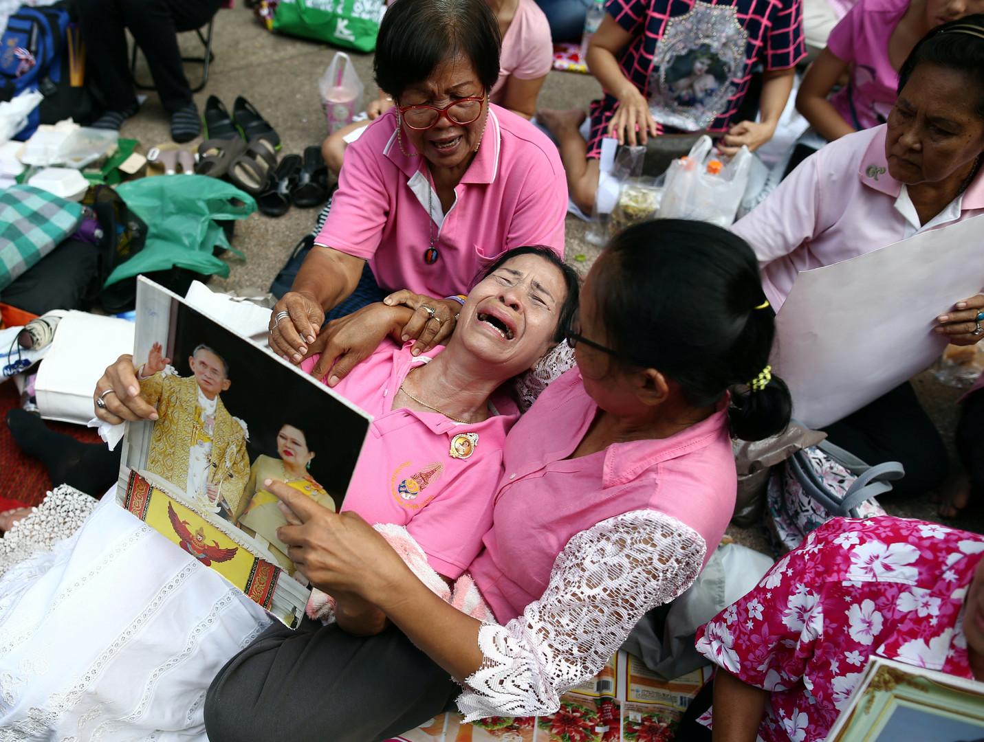 Тайцы плачут, молясь за здоровье короля Пхумипона Адульядета у больницы Сирират в Бангкоке, где он находился в последние дни жизни.