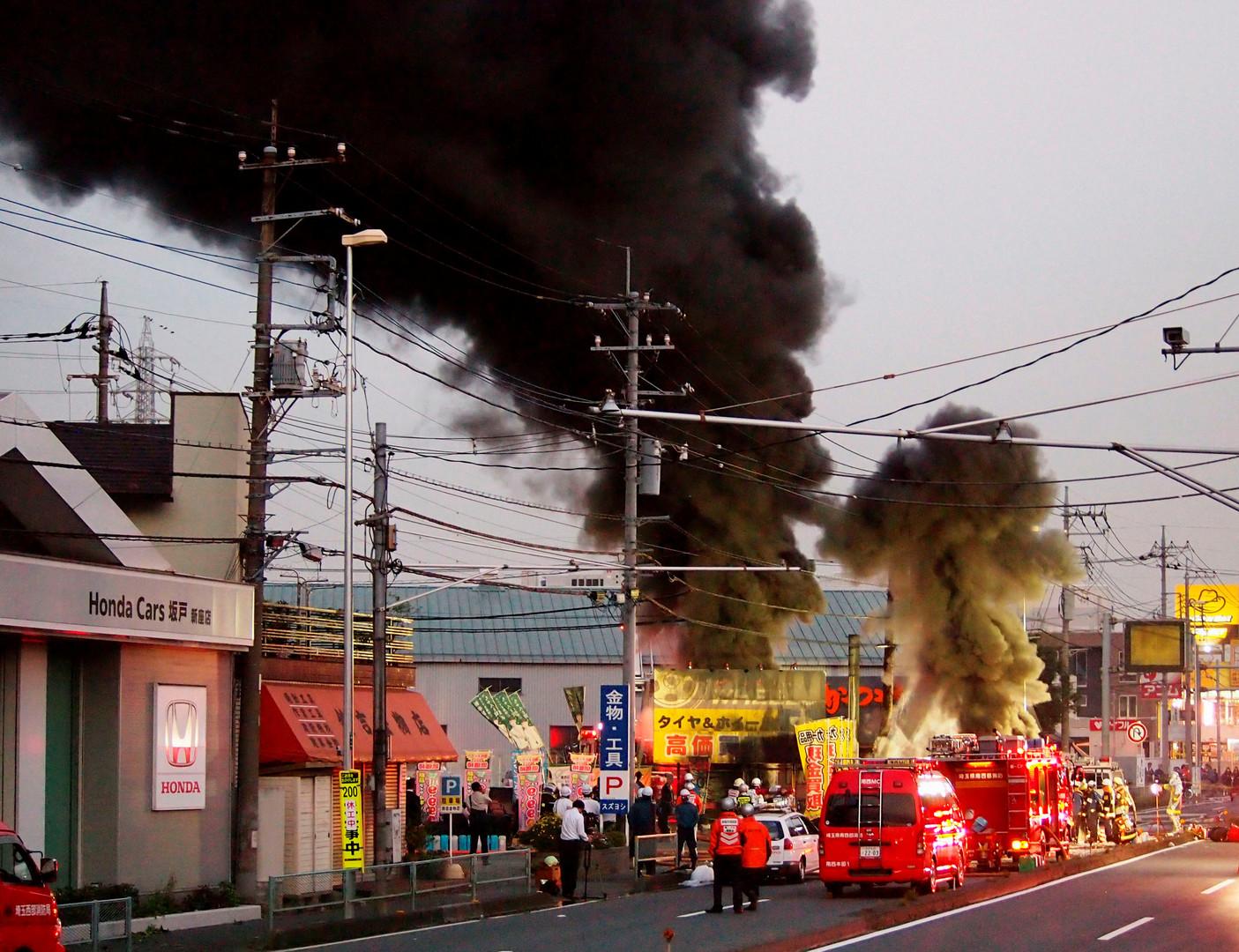 Пожарные на месте возгорания кабеля под землёй в японском городе Нииза.