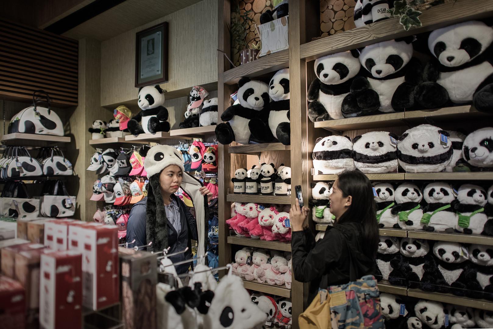 Туристы фотографируются в магазине сувениров рядом с парком развлечений, в котором жила Цзя Цзя. 28 июля 2015 года.