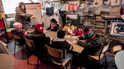 Дети на уроке в волонтерской школе в лагере для беженцев