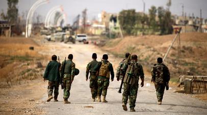 Бойцы пешмерга идут с оружием в сторону города Башика на востоке от Мосула, Ирак. 8 ноября 2016