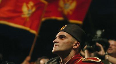 Солдат национальной гвардии на фоне флага Черногории перед зданием парламента в Подгорице