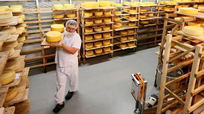 Фермер Олег Сирота занимается перекладкой головок сыра в хранилище созревания сыра сыроварни «Русский пармезан» в Истринском районе Московской области