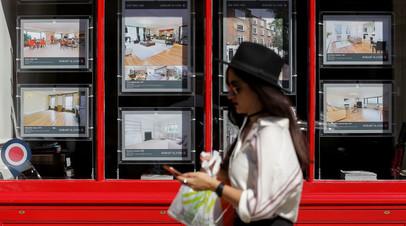 Женщина проходит мимо агентства недвижимости в Лондоне