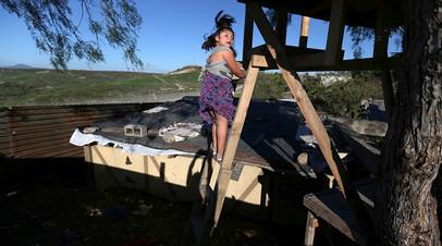 Девочка забирается на лестницу у забора на границе США и Мексики. Тихуана.