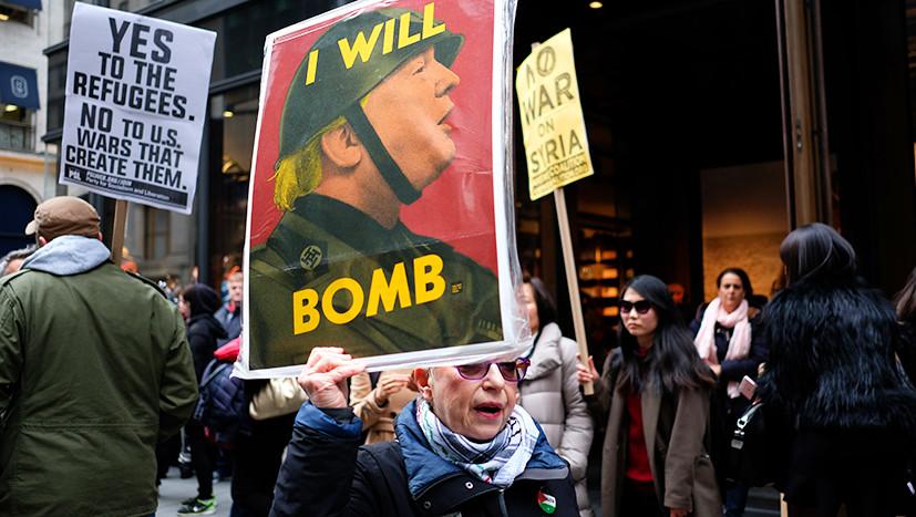 Протестующая с антитрамповским плакатом в Нью-Йорке